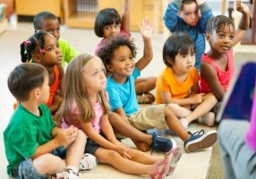 Diverse group of preschoolers listening to a story.